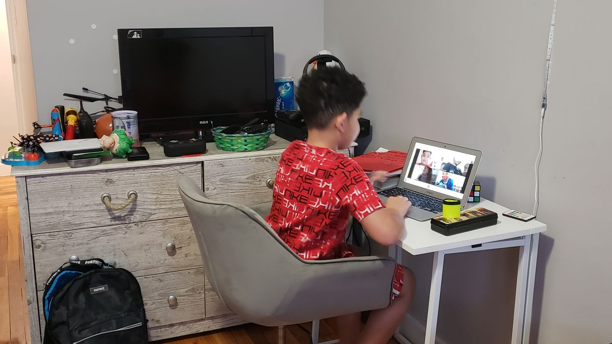 Frankie sitting at a desk looking at a laptop screen participating in a remote lesson.