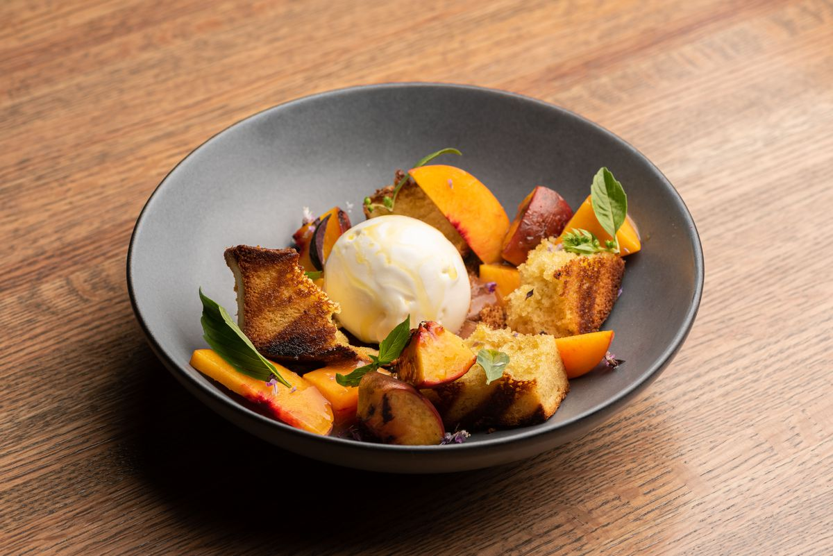 A grey bowl with a circle of ice cream with peaches and grilled bread.
