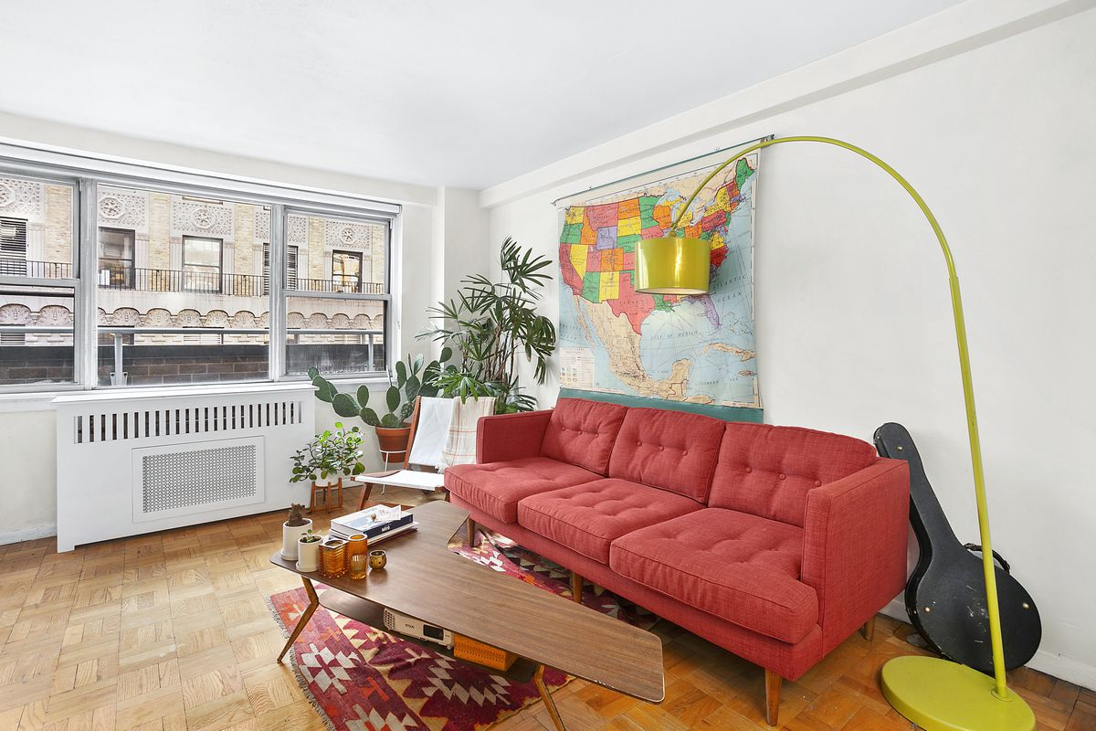 A living area with large windows, hardwood floors, a red bright couch, planters, and an arched yellow floor lamp.