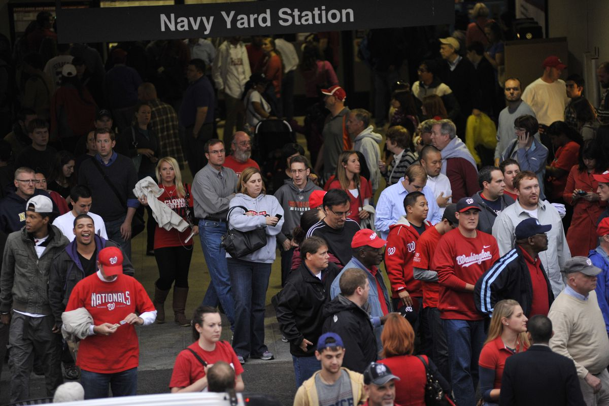 A large group of baseball fans exits a subway station.
