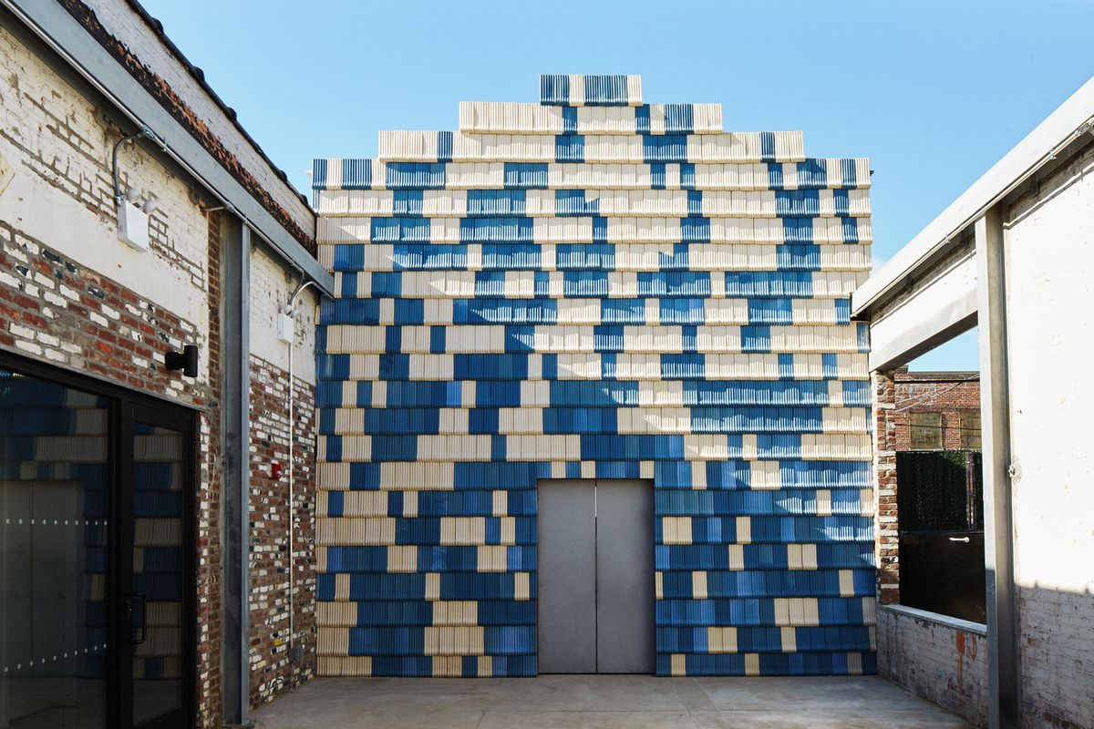 Exterior view of simple structure clad in blue and ivory-colored ridged tiles set against a brick warehouse space.