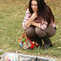 Jenni Thompson visits the grave of her husband, Bryce, at the Murray Cemetery in Murray  Nov 19, 2014. Several Thompson family members have died from cancer.