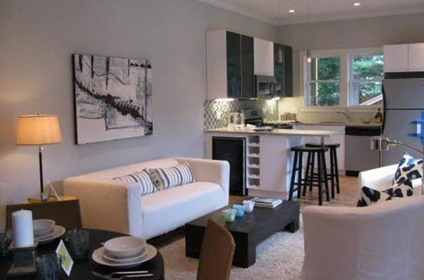 An open living room-kitchen with furniture.