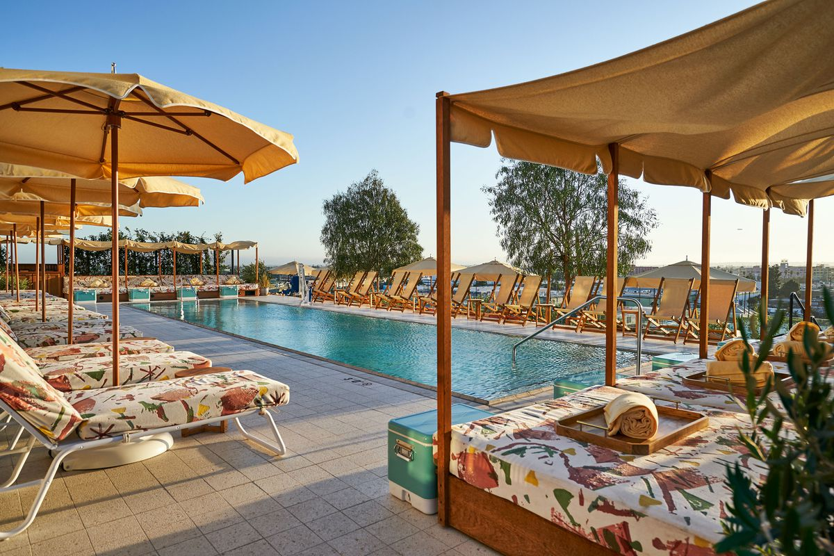 A large pool surrounding by lounge chairs and cabanas. The cushions for the seating is uniformly patterned.