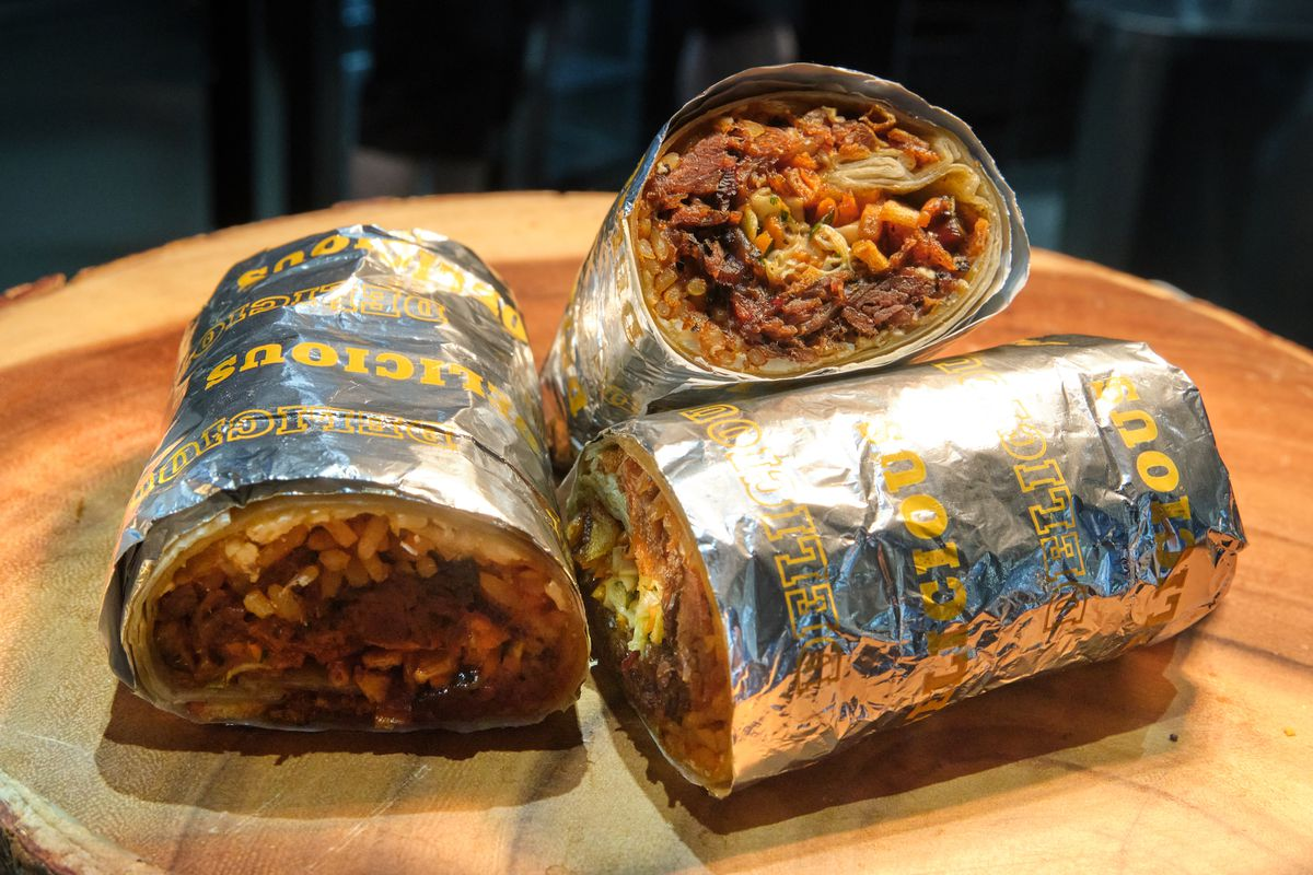 Three sliced burritos wrapped in aluminum foil on a wooden cutting board