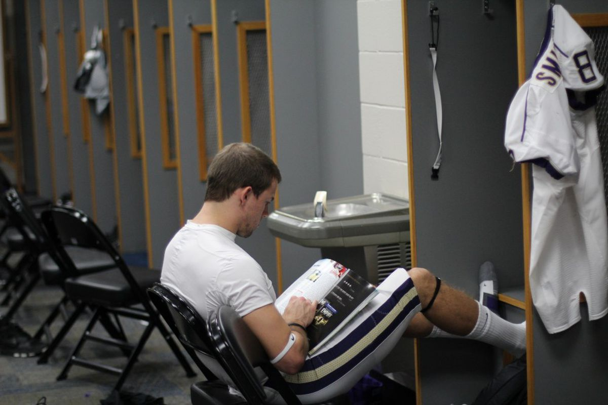 Cody Bruns gets a break to catch up on some reading at his locker.