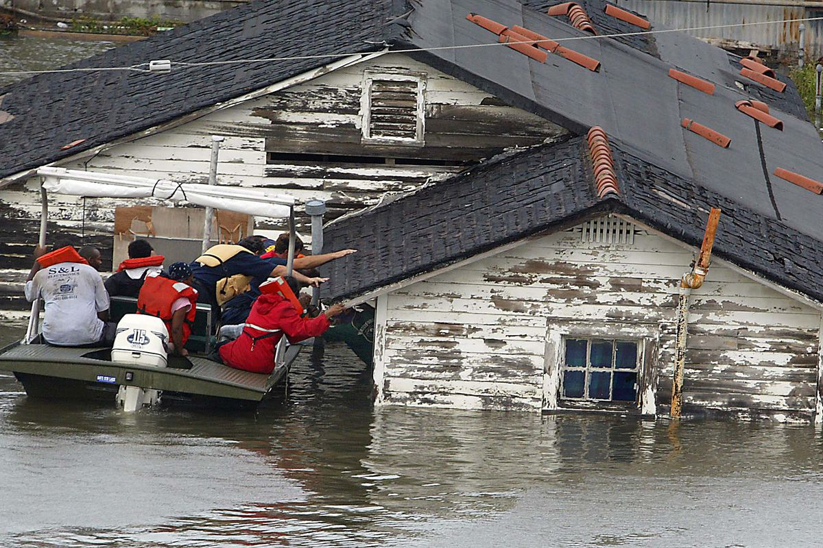 A man is rescued from his home in New Orleans after Hurricane Katrina.