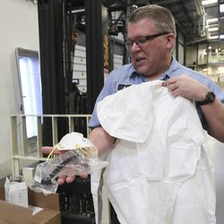 Bishop's Central Storehouse worker Adam Hunt holds a respirator mask, protective goggles and protective suit as The Church of Jesus Christ of Latter-day Saints prepares supplies to contributeto China in Salt Lake City, Utah, on Wednesday, Jan. 29, 2020.