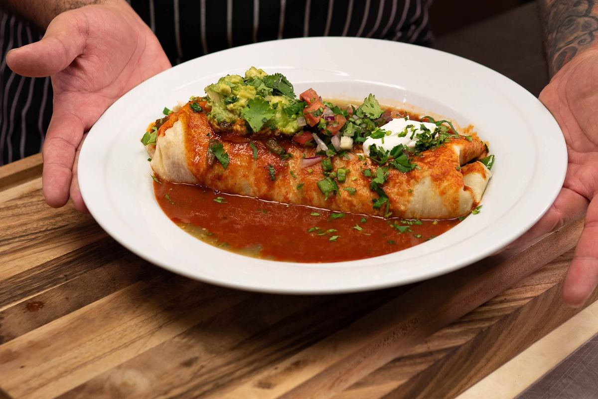 A wet burrito on a white plate held by two hands