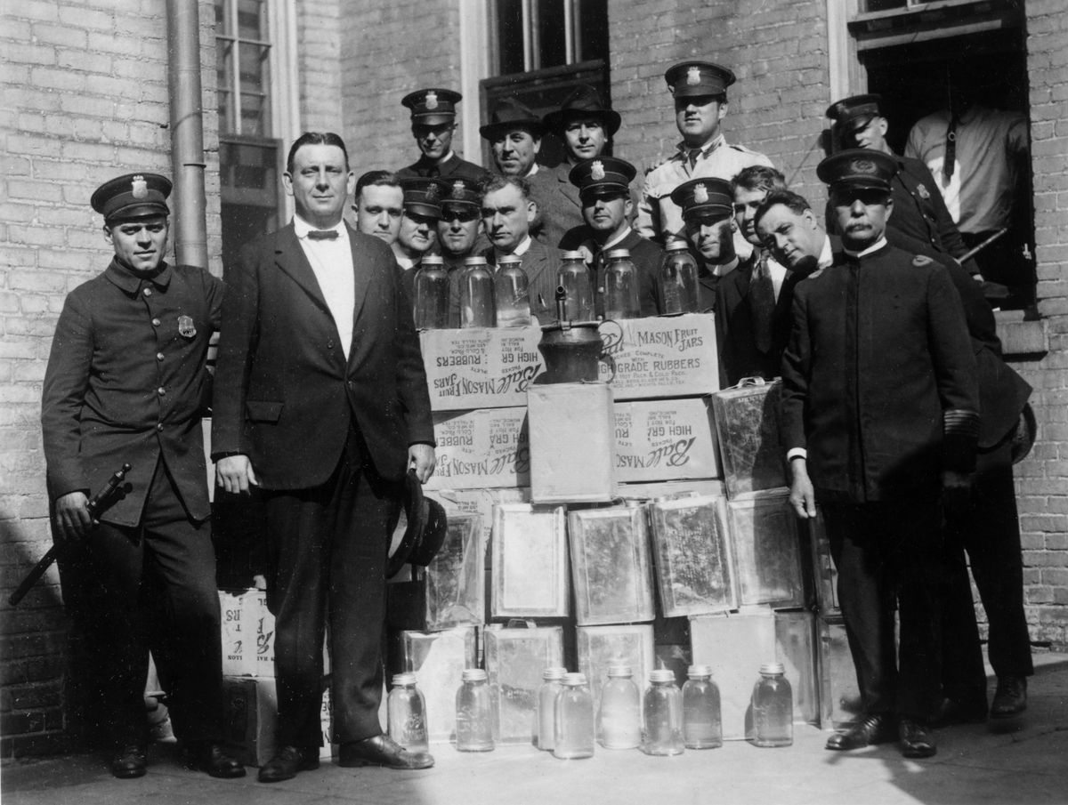 Police pose with confiscated liquor.