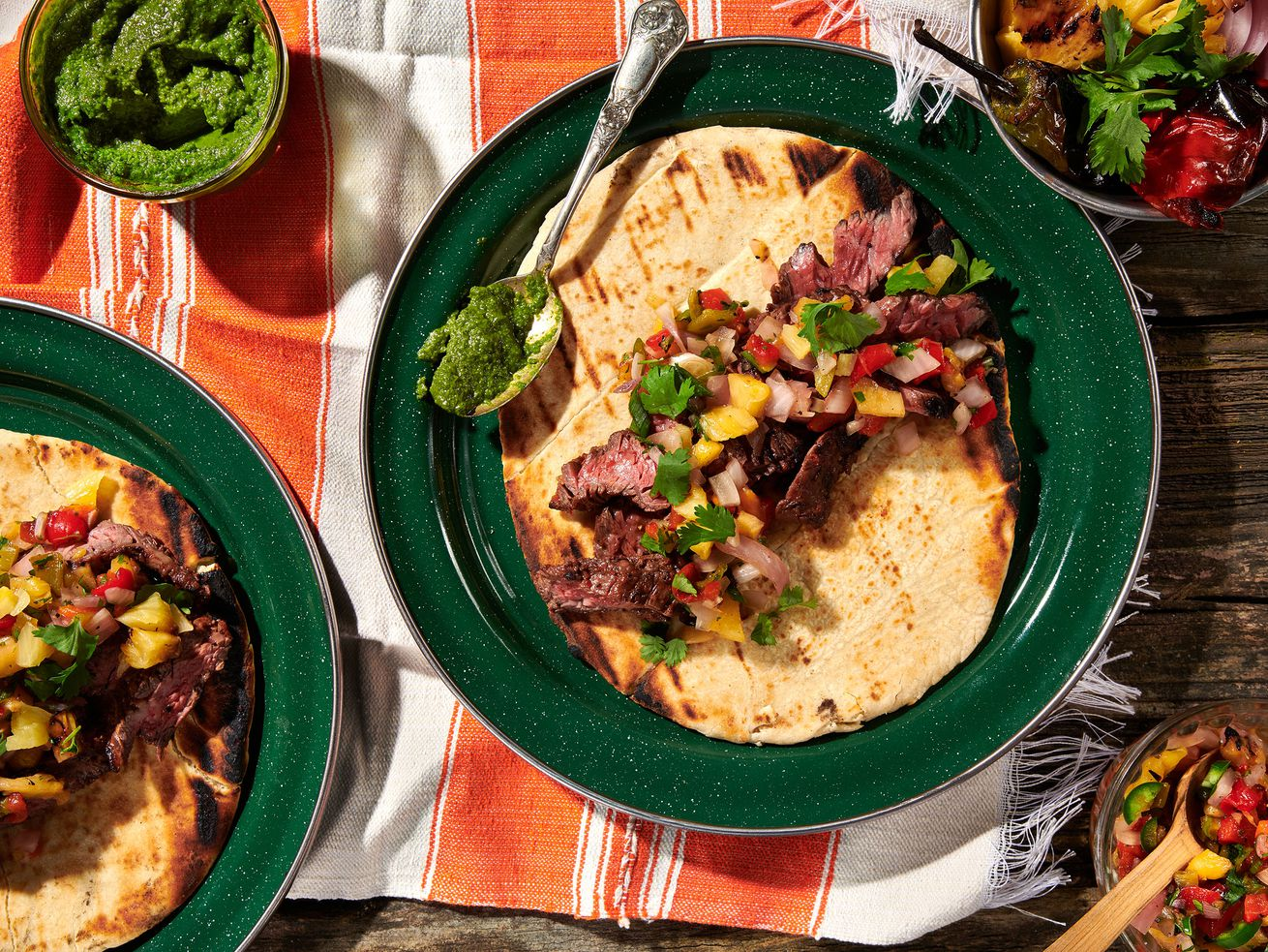 Skirt steak sliced and placed on top of naan, with pineapple, onion, and red pepper relish and chimichurri on top. Sides of roasted vegetables and a small bowl of chimichurri sit alongside.