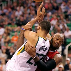 Utah Jazz center Rudy Gobert (27) gets pulled down by Los Angeles Clippers center Marreese Speights (5) during a basketball game at the Vivant Smart Home Arena in Salt Lake City on Monday, Oct. 17, 2016. Jazz won 104-78.