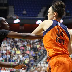 Connecticut Sun's Kelly Faris (34) is closely defended by Washington Mystics' Kahleah Cooper (2).