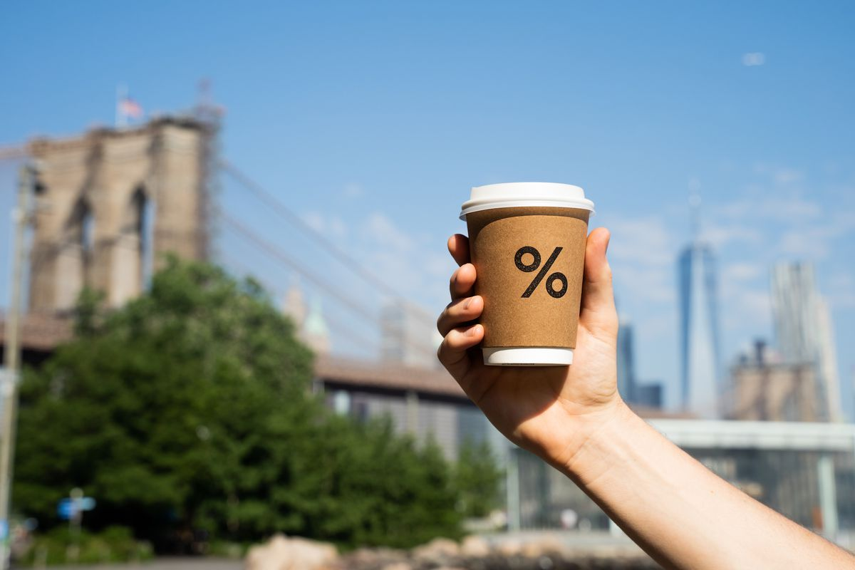 A hand holding a brown coffee cup emblazoned with the % Arabica logo, against a backdrop of the Brooklyn Bridge