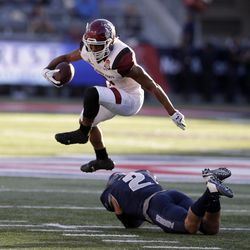 New Mexico State running back Larry Rose III (3) leaps over Utah State safety Dallin Leavitt in the first half during an NCAA college football bowl game, Friday, Dec. 29, 2017, in Tucson, Ariz. (AP Photo/Rick Scuteri)
