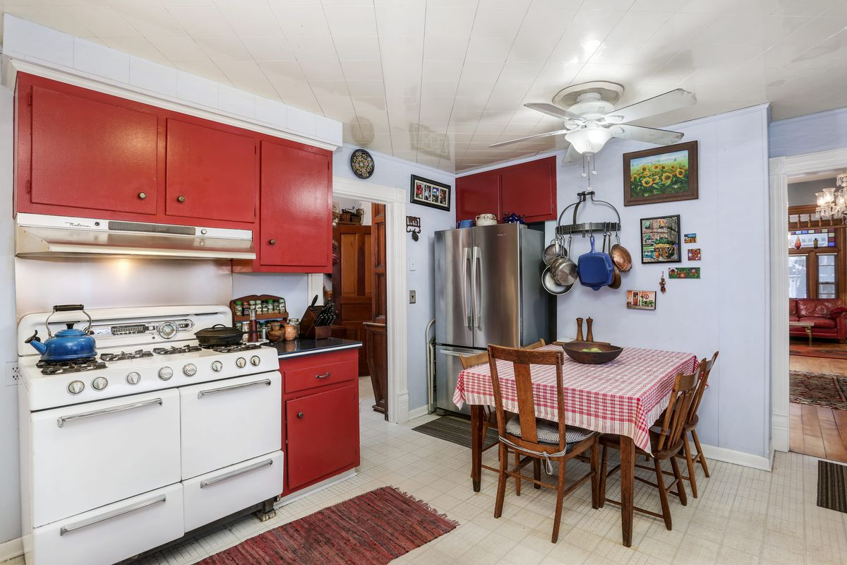 An older white stove and oven in between red-painted cabinets. A small dining table has a gingham tablecloth.