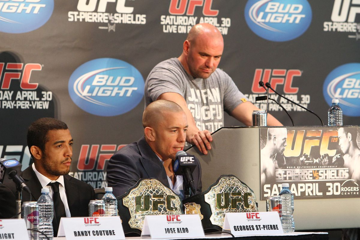 Georges St-Pierre speaks at the UFC 129 press conference flanked by Jose Aldo and Dana White.