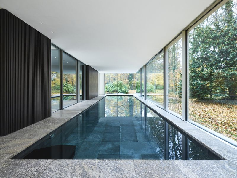 Pool surrounded by floor-to-ceiling windows.