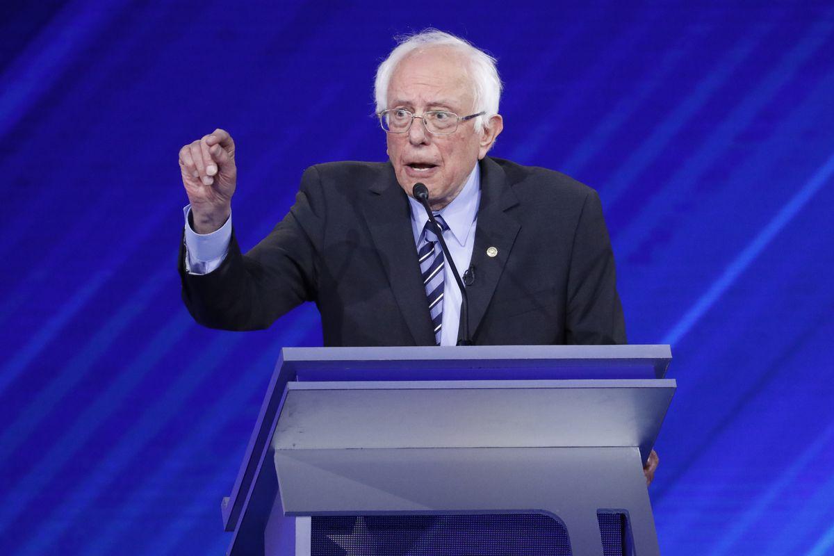Senator Bernie Sanders speaks at a rostrum during a Democratic primary debate.