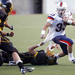 Timpview's Levi Teo tries to run out of the grasp of Cottonwood's Kyle Aberton in Friday's 4A title game in Salt Lake City.