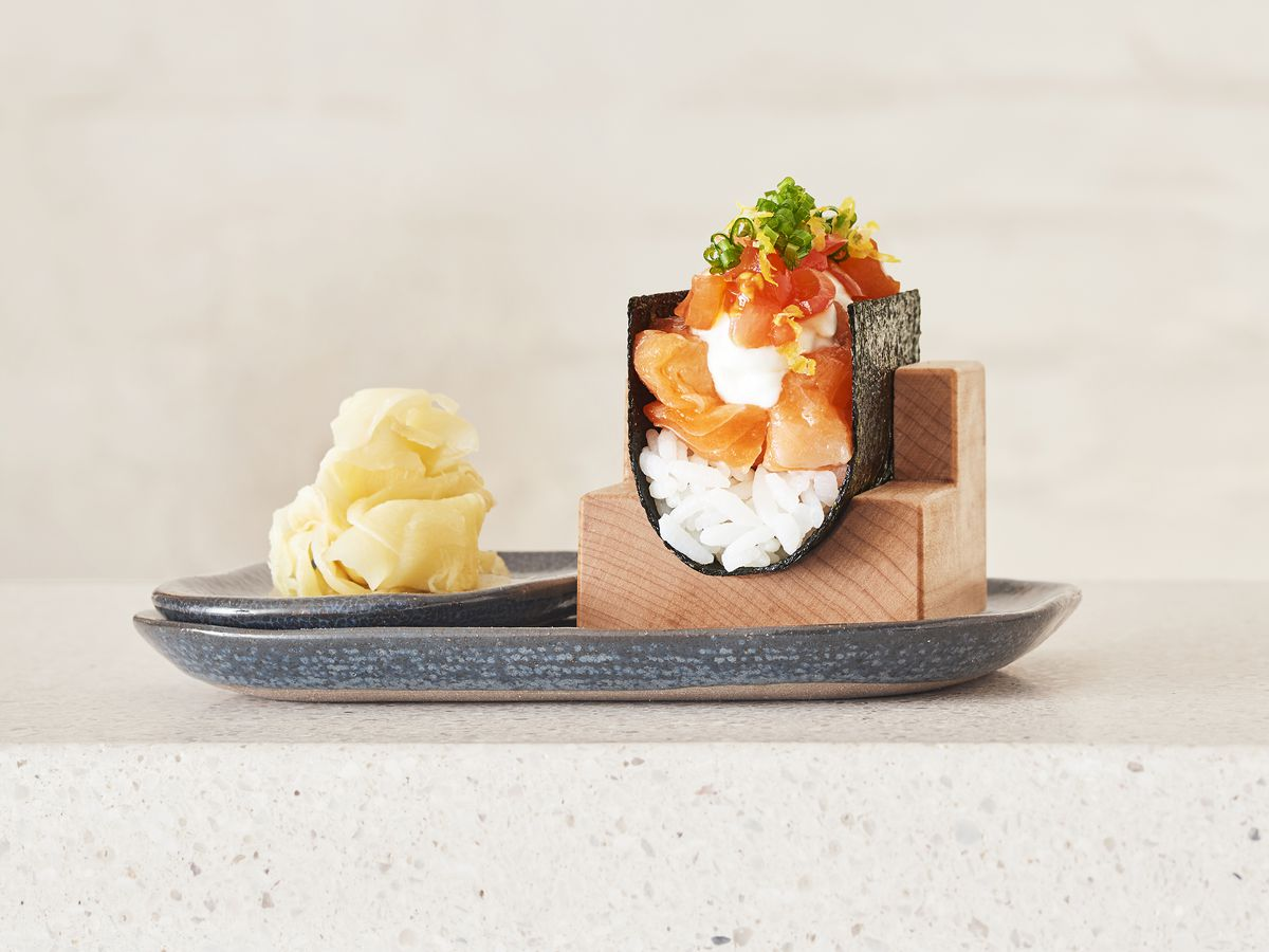 A taco-shaped hand roll topped with rice and salmon, served with a side of ginger
