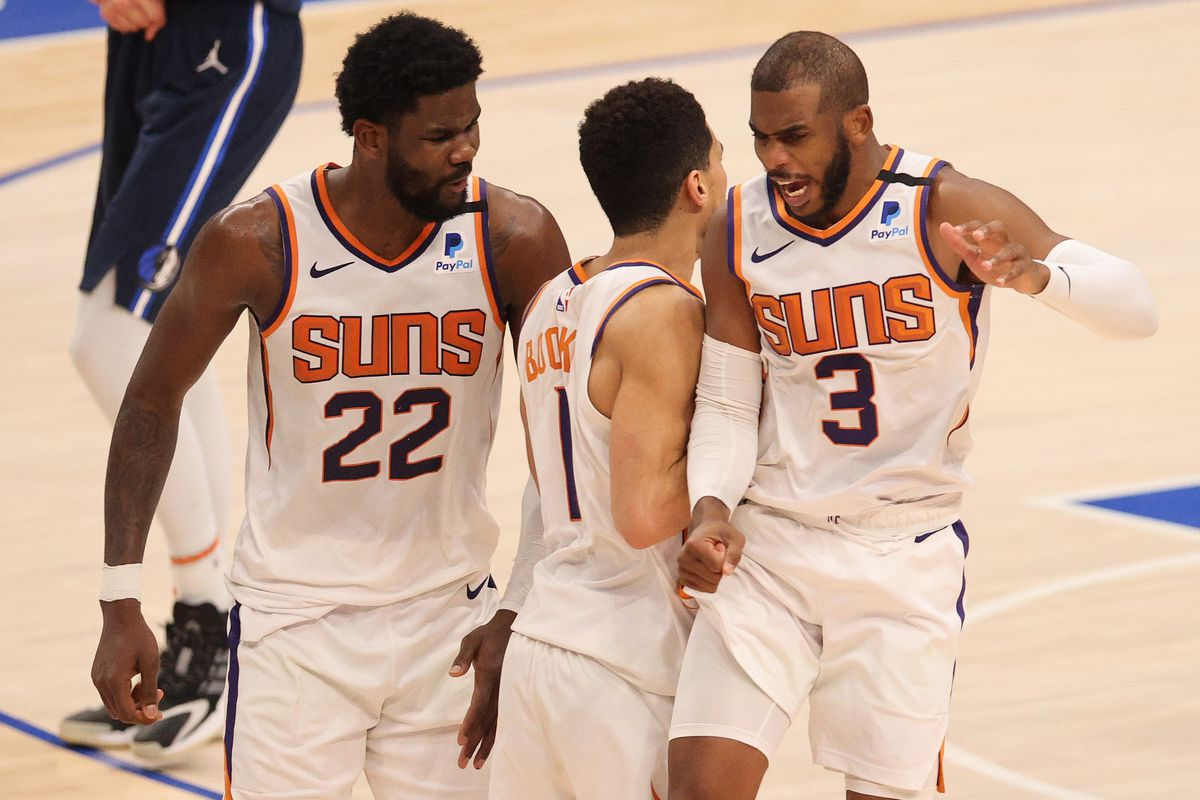 Devin Booker #1 celebrates the game winning shot with Deandre Ayton #22 and Chris Paul #3 of the Phoenix Suns against the Dallas Mavericks in the fourth quarter at American Airlines Center on February 01, 2021 in Dallas, Texas.