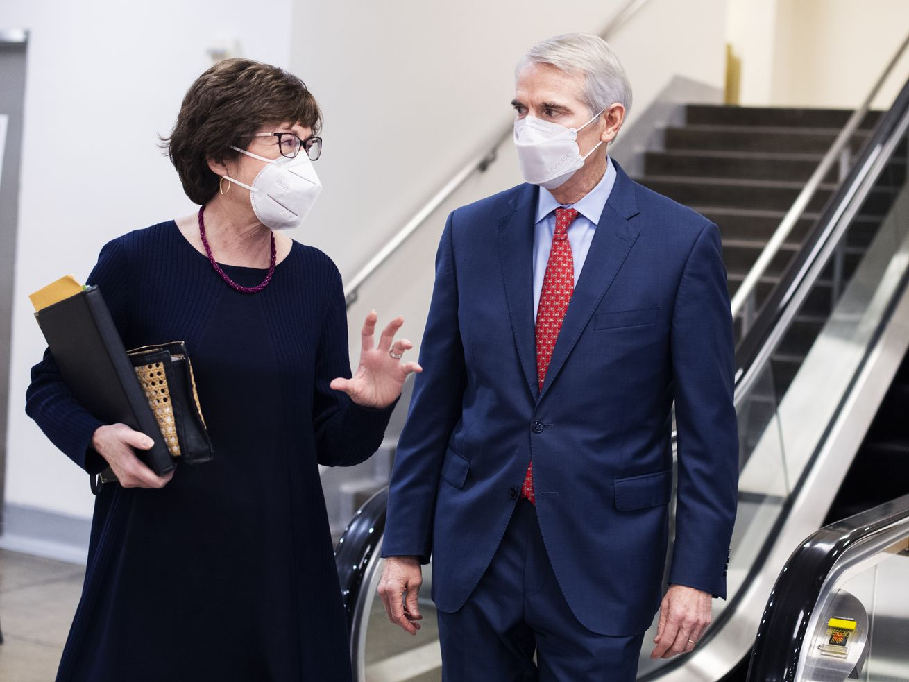 Collins, in a dark dress, gestures with her left hand while speaking to Portman, in a navy suit and red tie — they stand in front of an escalator near the Capitol subway, and both are wearing white KN95 masks.