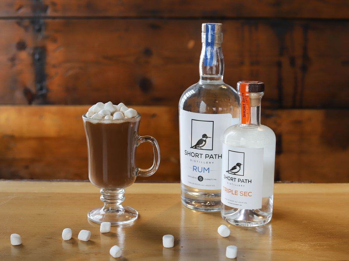 A boozy hot chocolate in a clear glass mug sits on a bar and is garnished with ample marshmallows. Bottles of Short Path Distillery rum and triple sec sit next to the cocktail.