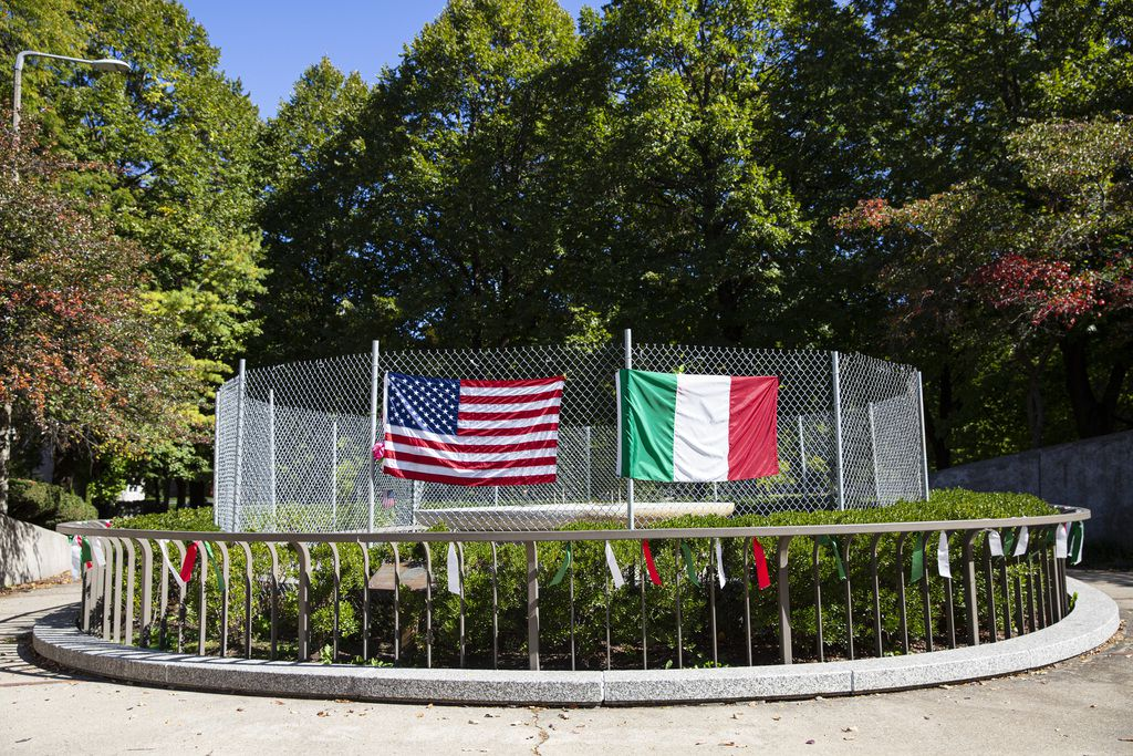 A fence with the U.S. and Italian flags cover the area where a Christopher Columbus statue once stood at Arrigo Park in University Village / Little Italy, Thursday, Oct. 8, 2020.