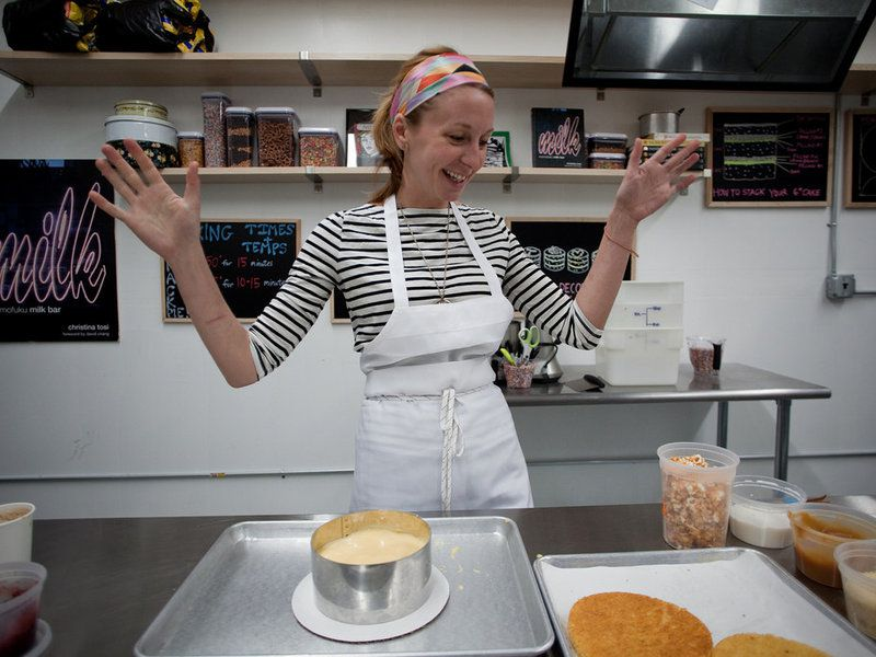 Christina Tosi, wearing a black-and-white horizontal striped long-sleeved shirt and a white apron, stands with her arms up in enthusiasm.