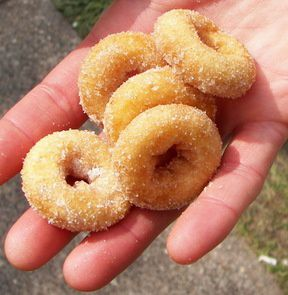 A hand holds tiny, sugar covered doughnuts