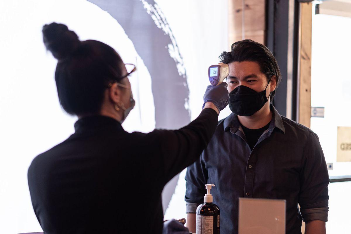 Employee at OMG checks temperature of guest walking into the Santa Ana sushi restaurant
