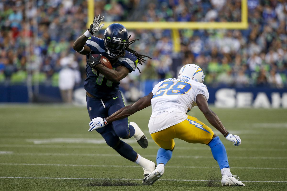 Seattle Seahawks running back Alex Collins (41) breaks a tackle against Los Angeles Chargers defensive back Brandon Facyson (28) during the first quarter at Lumen Field.