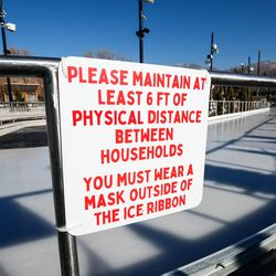 A social distancing reminder is posted at the new Bountiful Ice Ribbon at Bountiful Town Square in Bountiful on Saturday, Dec. 5, 2020.