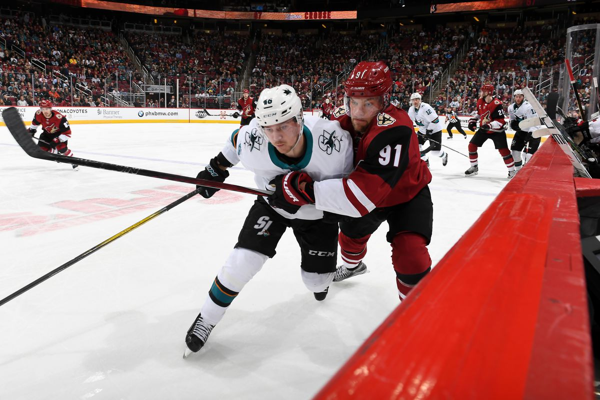 Taylor Hall #91 of the Arizona Coyotes and Joel Kellman #46 of the San Jose Sharks battle along the boards during the third period of the NHL hockey game at Gila River Arena on January 14, 2020 in Glendale, Arizona.