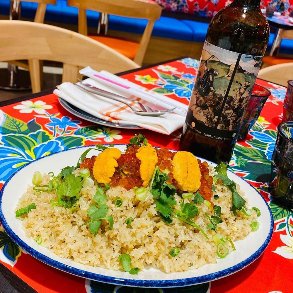 A fried rice dish next to a bottle of natural wine on a colorful table