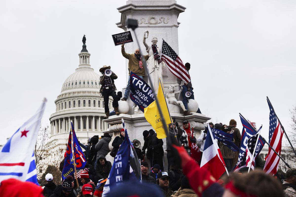 People wave flags and climb atop the base of a muniment in front of the US Capitol building.