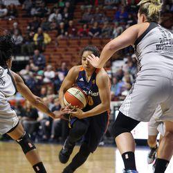 Connecticut Sun's Alex Bentley (20) drives through San Antonio Stars' Shamela Hampton (3) and Jayne Appel-Marinelli (32).