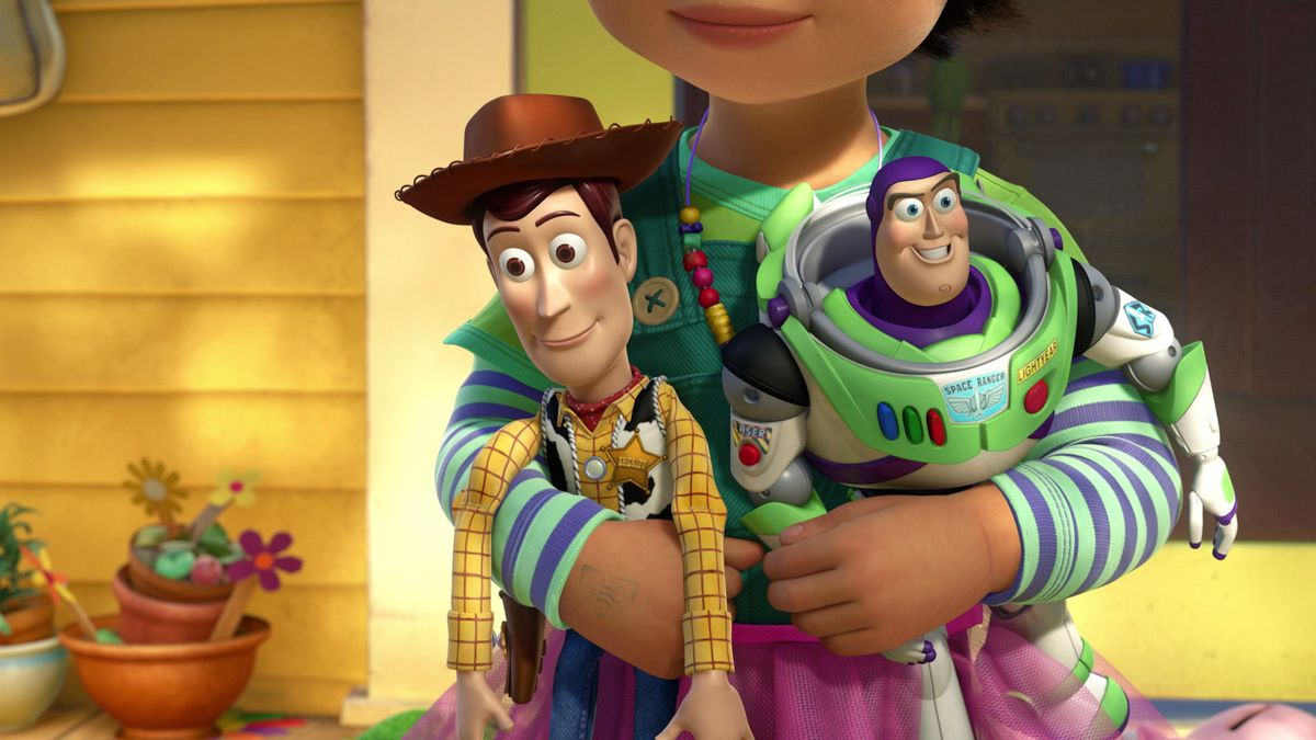 A small child, Bonnie, holds Woody (a cowboy action figure) and Buzz (a space ranger action figure)