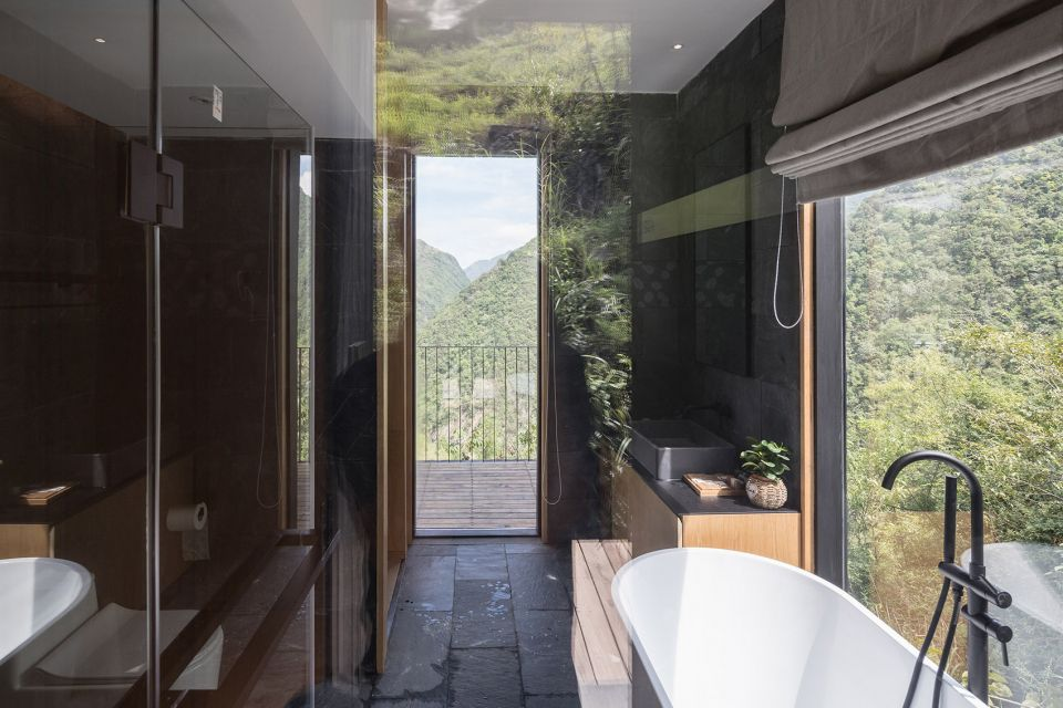 A bathroom in a cabin. There are dark stone floors, a white bathtub, and windows overlooking trees and mountains.