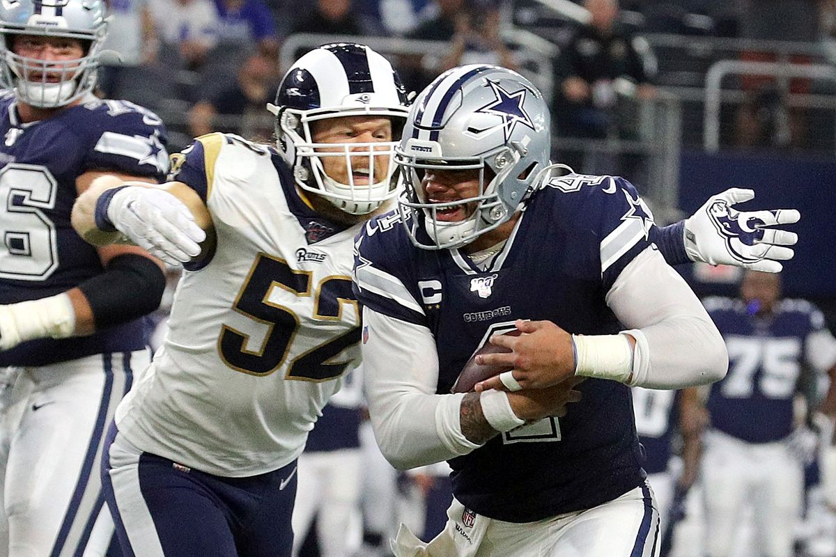 Clay Matthews of the Los Angeles Rams tries to stop Dak Prescott of the Dallas Cowboys at AT&T Stadium on December 15, 2019 in Arlington, Texas.