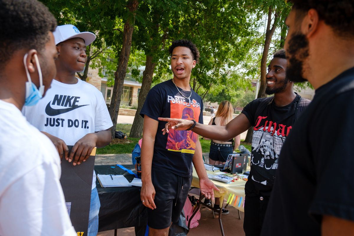 Five young friends, all men of color, have a conversation in front of a table for their student group.