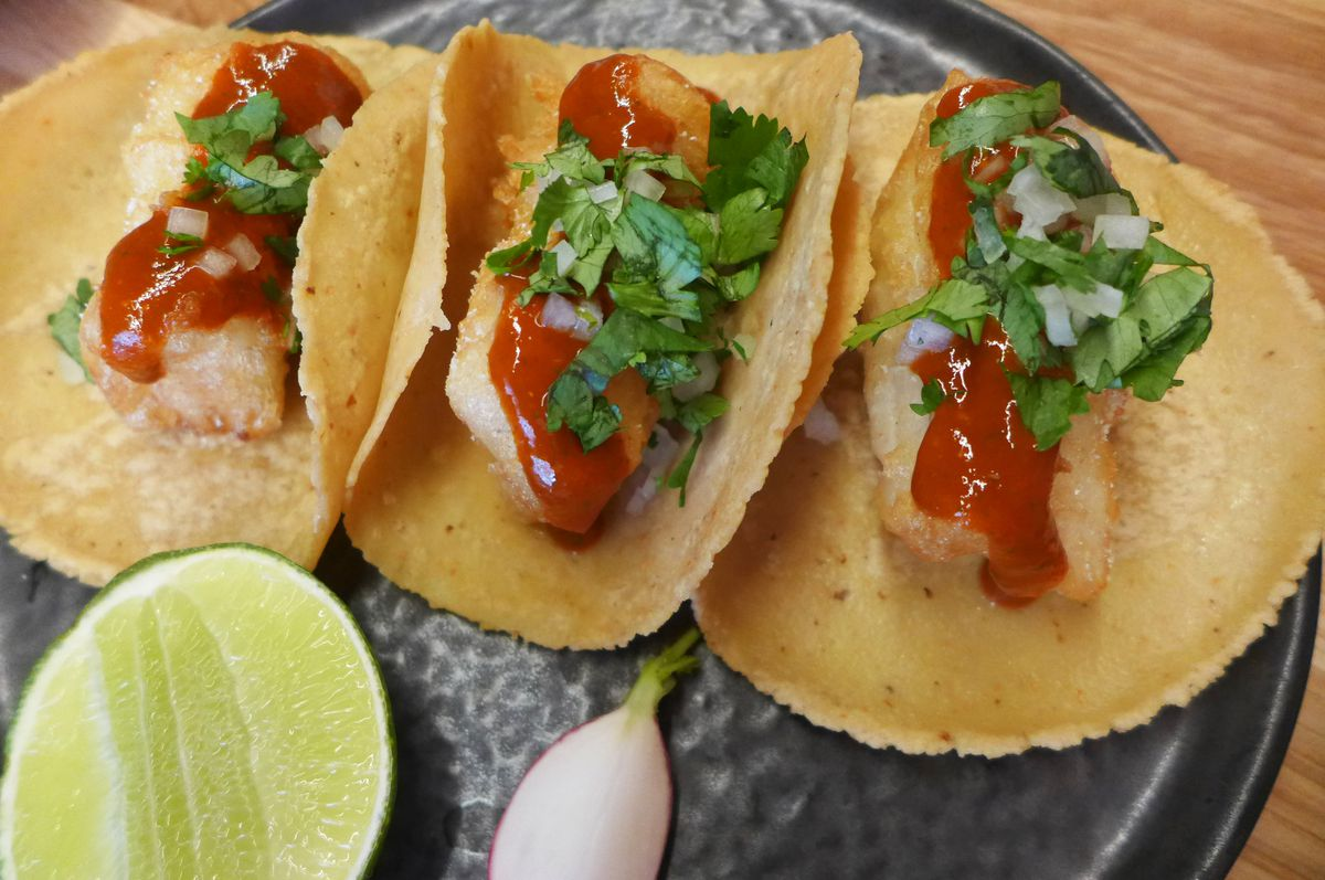 Three tacos cradling blocks of fried fish in each nearly obscured by a thick red sauce.