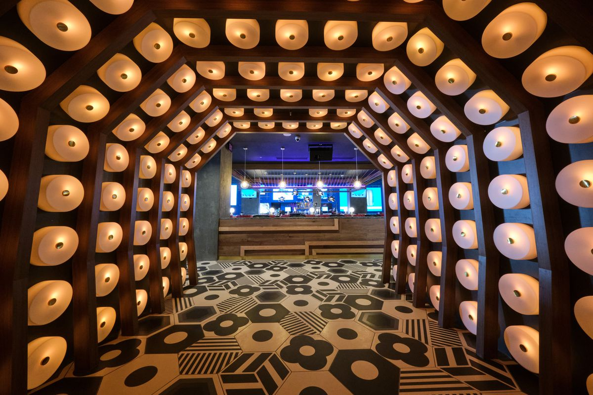 A bar entrance that looks like a tunnel with lights