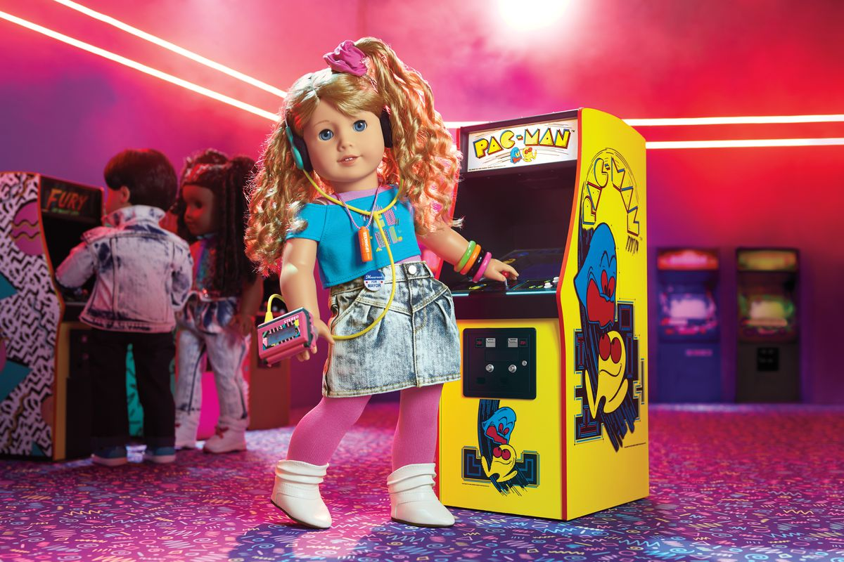 Courtney doll wears a walkman and stands in front of a Pac-Man cabinet