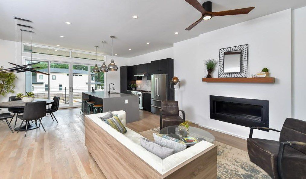A wide open living room and kitchen with white walls and a dark ceiling fan.