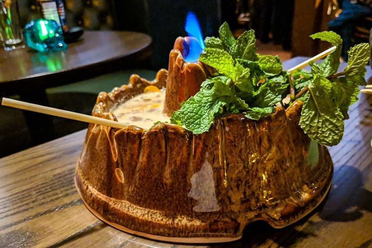A shareable cocktail is served in a tiki volcano vessel with a flame coming out of the top and a giant sprig of mint leaves