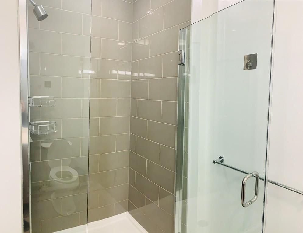 A shower with the glass door open.