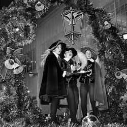 Singing Christmas carols, three boys clad in old English costumes add merriment in 1964.