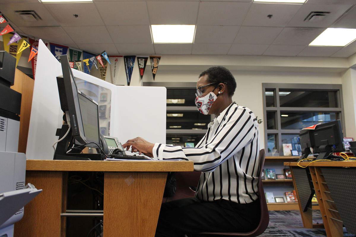 Woman in a striped shirt and wearing a mask sits at a desk working on a laptopl